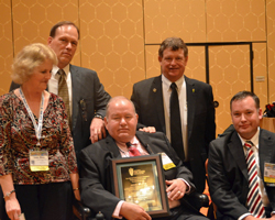 Jere White (center) with his wife Linda and son Robert, honored by NCGA CEO Rick Tolman and president Martin Barbre