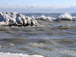 Ocean waves crash along an icy winter shoreline Photo @Redking
